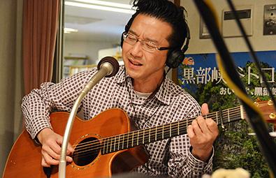 ギター演奏しながら歌うシンガー英樹さん