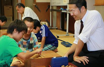 飛世将棋道場KUROBEで、子供達と将棋を指す桶屋郁夫さん