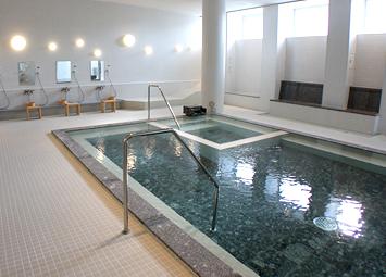 「月美の湯」の浴室。浴槽床に敷かれた黒部産の御影石がお湯に煌めきを与えます